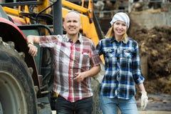 Agricoltori felici che lavorano al macchinario Immagine Stock