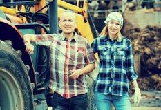 Agricoltori felici che lavorano al macchinario Fotografia Stock