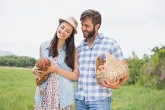Agricoltori felici che tengono pollo e le uova Immagini Stock
