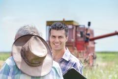 Agricoltori sul campo con il harbester dell'associazione Fotografie Stock