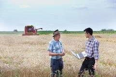 Agricoltori sul campo con il harbester dell'associazione Fotografia Stock