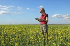 Agricoltura, agricoltore o agronomo nel giacimento del seme oleifero Fotografia Stock