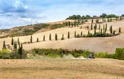 Agricoltura che ara trattore con un aratro del coltivatore il campo dopo il raccolto Fotografie Stock Libere da Diritti