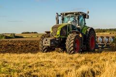 Agricoltura che ara trattore sui giacimenti del cereale del frumento Fotografia Stock Libera da Diritti