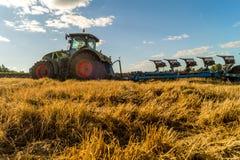 Agricoltura che ara trattore sui giacimenti del cereale del frumento Fotografie Stock Libere da Diritti