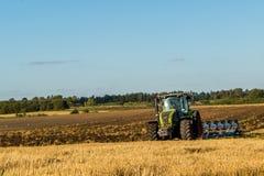 Agricoltura che ara trattore sui giacimenti del cereale del frumento Immagine Stock Libera da Diritti