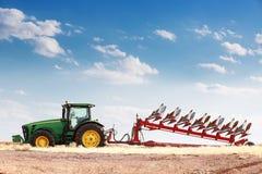 Agricoltura che ara trattore sul giacimento di cereale del grano Fotografia Stock Libera da Diritti
