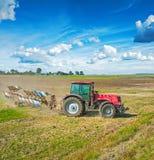Agricoltura che elabora trattore con l'aratro sul campo in autunno Fotografie Stock Libere da Diritti