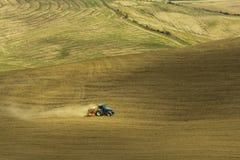 Agricoltura del trattore nei campi della Toscana Immagine Stock