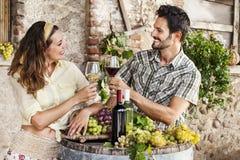 Agricoltura del vino bevente delle coppie nella loro vecchia azienda agricola Immagini Stock