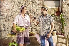 Agricoltura delle coppie che producono un pane tostato con un bicchiere di vino, tempo di raccolto Fotografia Stock