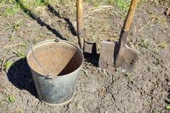 agricoltura due pale e un secchio del ferro lavoro della molla sul immagine stock