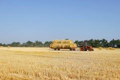 Agricoltura - il trattore porta un mucchio di fieno Trattore con fieno Immagini Stock Libere da Diritti