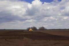 agricoltura Il trattore prepara il campo per la semina del grano dentro Immagine Stock