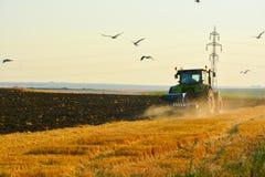 Agricoltura moderna con il trattore nel campo arato Fotografia Stock