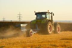 Agricoltura moderna con il trattore nel campo arato Fotografie Stock