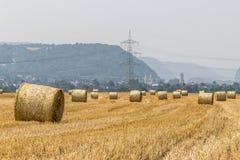 Agricoltura raccolta del campo con le balle della paglia durante l'estate Germania vicino a Andernach Immagini Stock Libere da Diritti