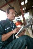 Agriculteur à l'aide du comprimé dans la grange Photographie stock libre de droits