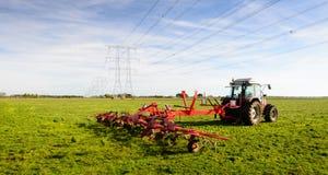Agriculteur au travail avec une faneuse de foin Images stock