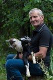 Agriculteur aux cheveux gris de sourire tenant deux chèvres de bébé dans des ses bras photos stock