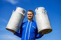 Agriculteur avec des récipients de lait Photo stock