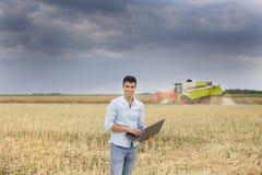 Agriculteur avec l'ordinateur portable dans le domaine Photo stock