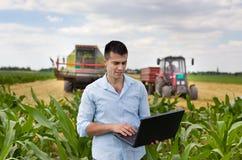 Agriculteur avec l'ordinateur portable pendant la récolte Photographie stock libre de droits