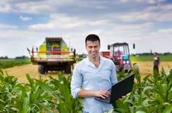 Agriculteur avec l'ordinateur portable pendant la récolte Photographie stock