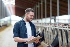 Agriculteur avec le presse-papiers et les vaches dans l'étable à la ferme Photo stock
