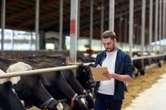Agriculteur avec le presse-papiers et les vaches dans l'étable à la ferme Photos stock
