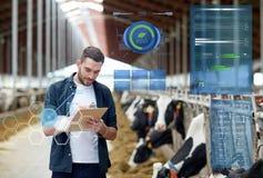 Agriculteur avec le presse-papiers et les vaches dans l'étable à la ferme Images libres de droits