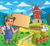 Agriculteur avec le signe près du moulin à vent Photographie stock