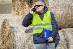Agriculteur avec le smartphone et dossier près des balles de foin Photos libres de droits