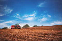 Agriculteur avec le tracteur semant des cultures au champ Photographie stock