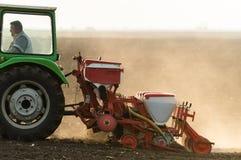 Agriculteur avec le tracteur semant des cultures de soja au champ agricole images libres de droits
