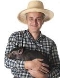 Agriculteur avec un petit porc noir Photos stock
