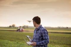 Agriculteur conduisant le bourdon au-dessus du champ photos stock