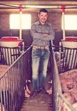 Agriculteur d'homme se tenant dans la porcherie Photos stock