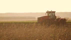 Agriculteur dans la terre de préparation moulue de sol d'agriculture de la Russie de tracteur avec le cultivateur de semis en tan clips vidéos