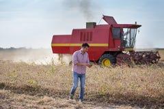Agriculteur dans le domaine de soja pendant la récolte photographie stock libre de droits