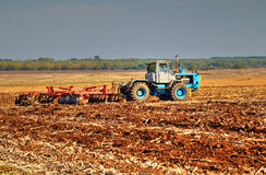 Agriculteur dans le tracteur préparant la terre Photos stock