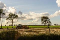 Agriculteur dans le tracteur préparant la terre avec le cultivateur de semis Coucher du soleil images libres de droits