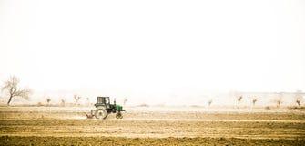 Agriculteur dans le vieux tracteur préparant la terre avec le cultivateur de semis photo libre de droits