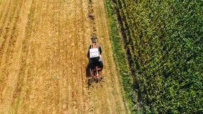 Agriculteur de moissonneuse à l'aide du tracteur avec les râteaux rotatoires pour rassembler le foin Vue aérienne de bourdon, dét image libre de droits