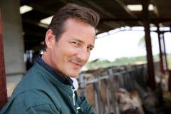 Agriculteur de sourire dans la grange Image libre de droits