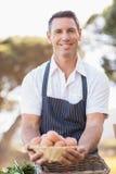 Agriculteur de sourire tenant un panier des oeufs Image stock