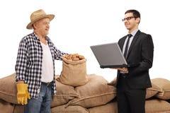 Agriculteur et un homme d'affaires avec un ordinateur portable devant une pile de bureau Photos stock