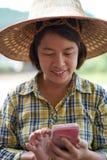 Agriculteur féminin de portrait à l'aide du smartphone dans le domaine de riz de tache floue et le m Photographie stock libre de droits