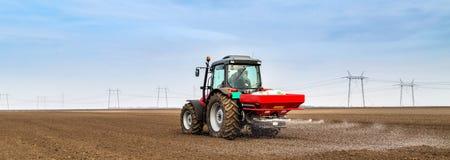 Agriculteur fertilisant les terres arables avec de l'azote, phosphore, engrais de potassium Photos stock