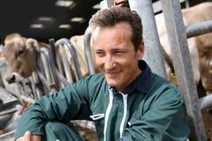 Agriculteur heureux de sourire s'asseyant dans la grange Image stock